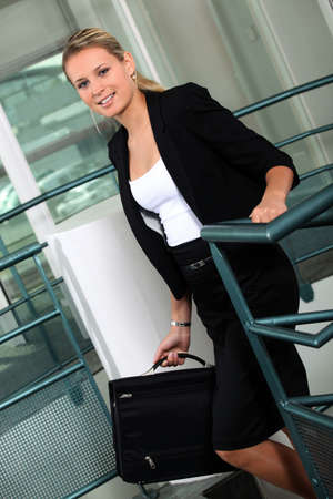 Businesswoman with briefcase climbing steps