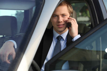 junior executive on the phone driving luxury car photo