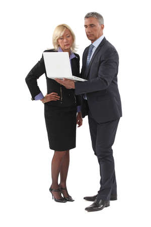 mature businessman standing with laptop and female counterpart photo