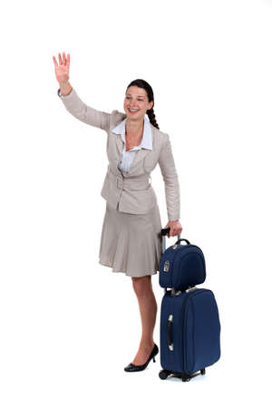 Woman with a suitcase waving at someone photo