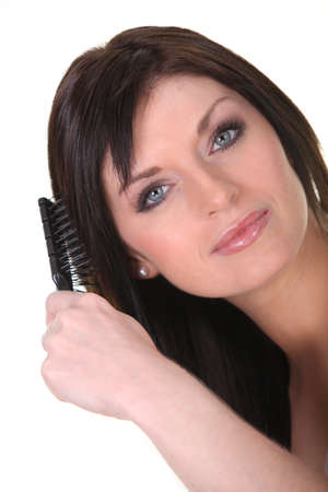 Studio shot of a brunette brushing her hair photo
