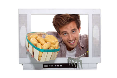 Boy with basket of potatoes behind television frame