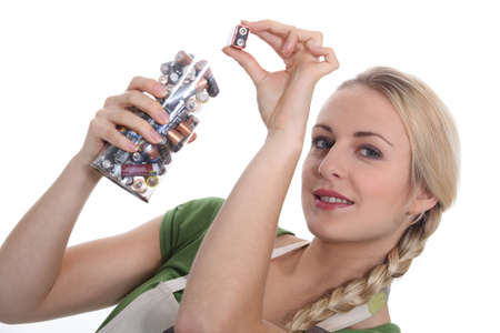 reprocessing: a blonde woman collecting batteries for recycling Stock Photo