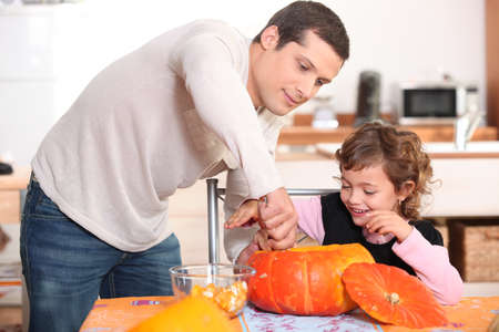 single father: Father and daughter carving pumpkins