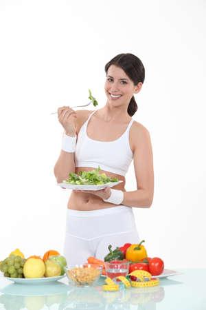plateful: Woman eating a plateful of salad leaves