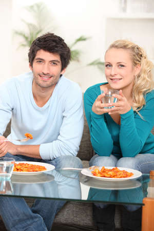 young couple eating ravioli photo