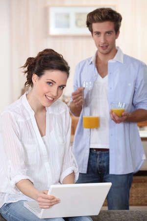 Couple drinking orange juice whilst using laptop photo