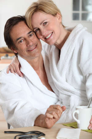 house robe: Couple dressed in bathing robes in the kitchen Stock Photo