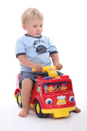 kleiner Junge sitzt auf einem Spielzeugauto Standard-Bild