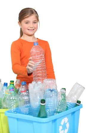 Young girl recycling plastic bottles photo
