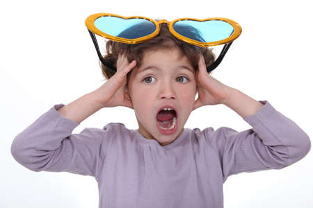 Little girl screaming with huge funny sunglasses on head photo
