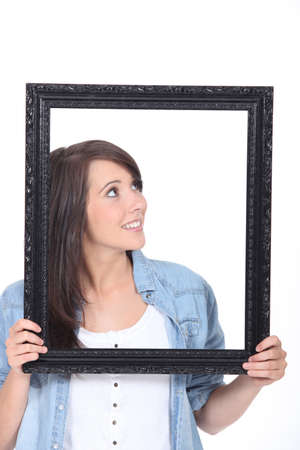 Woman stood holding empty picture frame photo