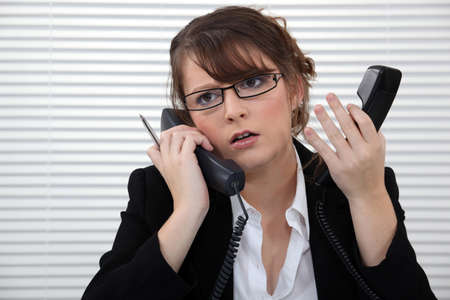 Stressed office worker with two telephones photo