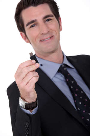portrait of executive all smiles holding usb drive photo
