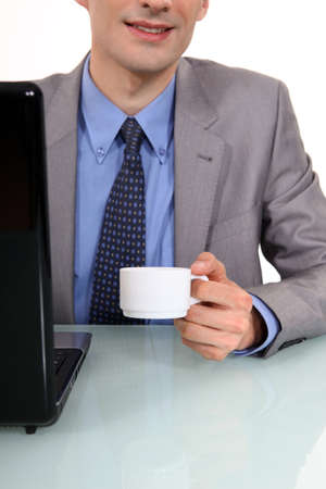 Businessman sat at laptop with morning coffee photo