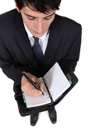 scheduling: Businessman scheduling an appointment into his agenda Stock Photo