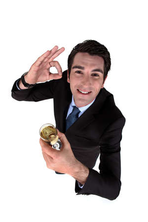Businessman drinking a glass of wine and giving the a-ok gesture