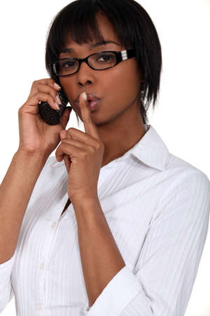 black bespectacled woman on the phone with finger before her mouth Stock Photo - 13542079