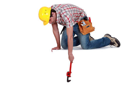 Worker reaching down with a wrench photo