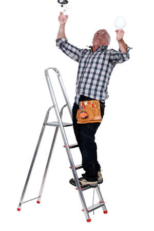 burned out: Electrocuted man changing a light bulb Stock Photo