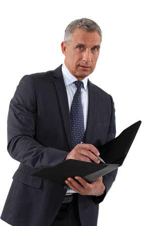 Businessman writing in a folder photo