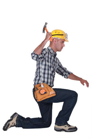 kneeling man: carpenter in profile using hammer Stock Photo