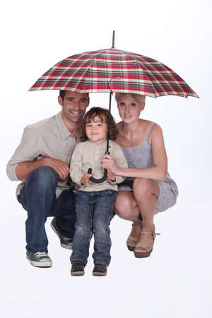 Young family crouching under an umbrella photo