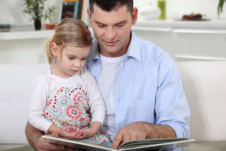 young father reading his daughter story photo