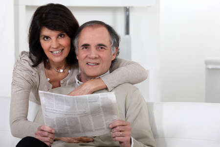 Mature couple looking at a newspaper photo