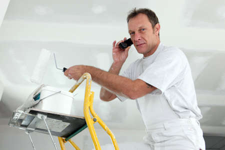 painter on ladder making a call Stock Photo