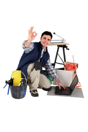 Tiler with laptop giving the all-clear Stock Photo - 13561357