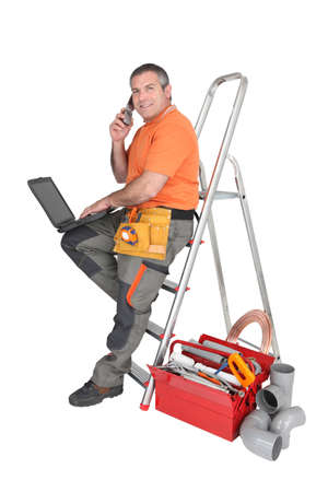 artisan: Manual worker surrounded by equipment Stock Photo