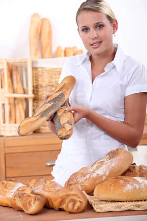Assistant in a bakery offering poppy seeded baguettes photo