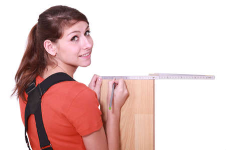 female woodworker measuring a board photo