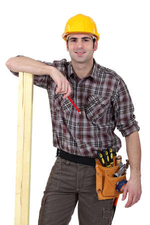 Carpenter about to mark wood with pencil Stock Photo