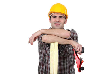 carpenter's sawdust: Carpenter posing with plank of wood and plane