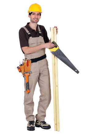Worker holding plank of wood and hand-saw photo