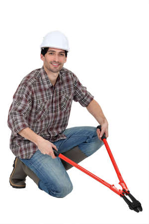 Man kneeling with bolt-cutters Stock Photo - 13560862