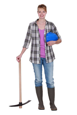 Woman construction worker standing with a pickaxe photo