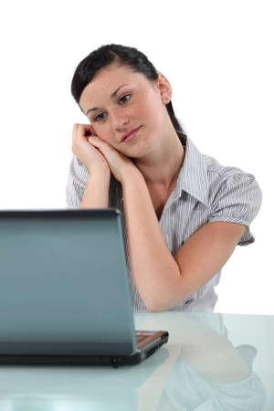 Happy brunette sitting at her desk Stock Photo - 13560792