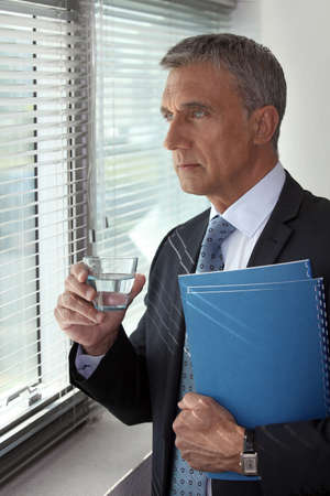 55 to 60: Businessman looking through his office window