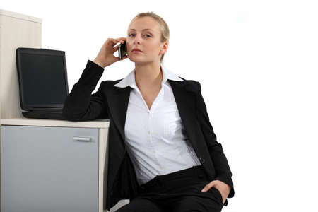 Serious blond businesswoman making a call Stock Photo