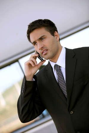 investor: Concerned businessman holding cellphone