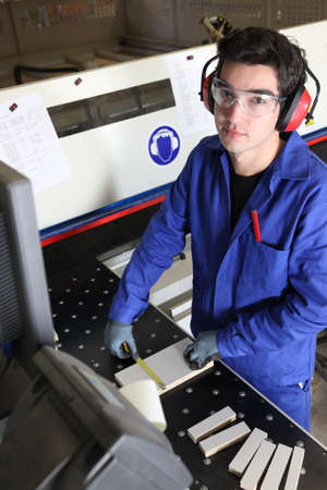 Young factory worker operating cutting machine photo