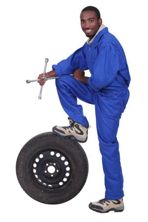 cross leg: blue collar holding cross faucet with leg resting on pneumatic tyre