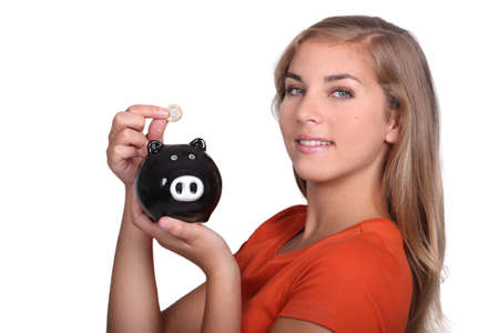 Teenager placing money in piggy bank Stock Photo - 13560788
