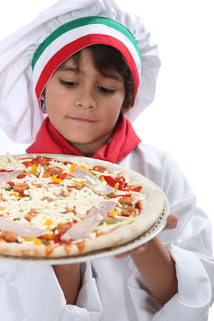 tantalizing: Young boy pretending to a be a pizza maker