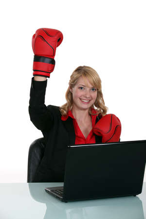 Happy businesswoman with gloves for boxing photo