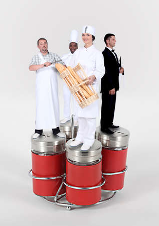 sharpening: workers of food and catering trade standing on giant salt cellar and pepperpot Stock Photo