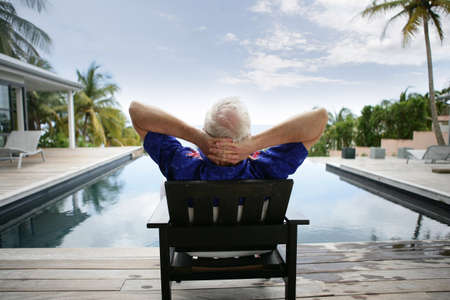 sunbathing: Older man relaxing by a luxurious pool